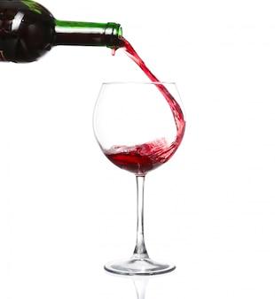 Rode wijn die in wijnglas gieten dat op wit wordt geïsoleerd