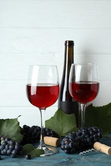 Rode wijn, druif, kurk en kurkentrekker op houten tafel