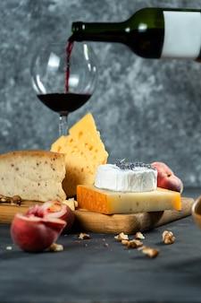 Rode wijn en kaas. verschillende soorten kaas met noten, lavendel en vijgen perzik op snijplank. romantisch diner. kopieer ruimte voor ontwerp. donkere achtergrond. zachte focus. giet wijn in een glas