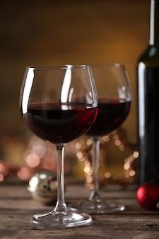 Rode wijn en kerst ornamenten op houten tafel op houten achtergrond