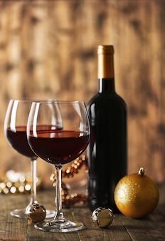 Rode wijn en kerstversieringen op houten tafel op houten oppervlak