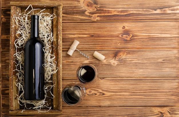 Rode wijn fles kurkentrekker kurken wijnglazen op houten tafel met kopie ruimte. rode wijn samenstelling op bruin houten tafel. bovenaanzicht.