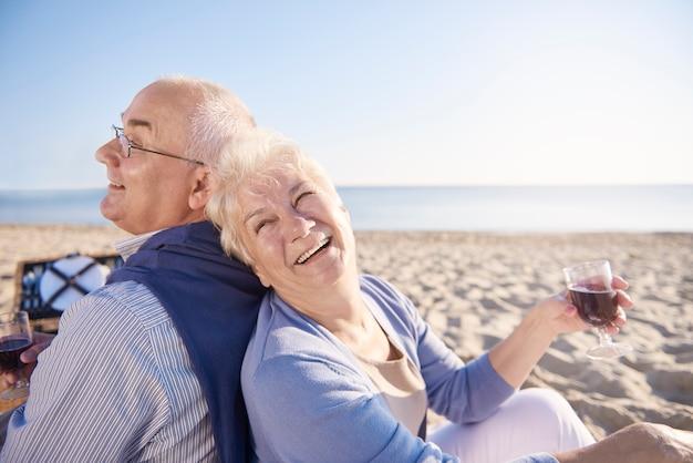 Rode wijn gedronken op het strand. senior paar in het strand, pensioen en zomervakantie concept