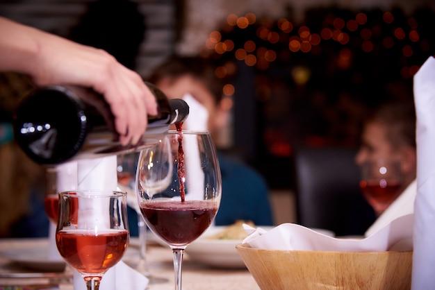 Rode wijn giet in een wijnglas op een onscherpe achtergrond.