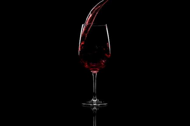 Rode wijn gieten in een wijnglas, over zwart