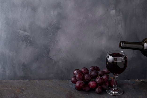 Rode wijn gieten in glas uit fles kopieer de ruimte