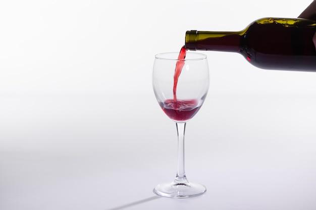 Rode wijn, gieten in glas uit fles op witte achtergrond met kopie ruimte