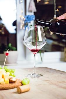 Rode wijn gieten in het glas. kaas plankje. thuisfeest met wijn