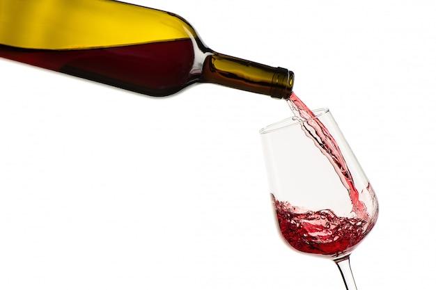 Rode wijn, gieten van fles in glas op een witte achtergrond