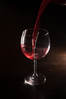 Rode wijn in beweging op zwarte achtergrond. alcohol reclame close-up, voortreffelijke drank gieten in wijnglas. lekkere alcoholische drank, commercieel concept