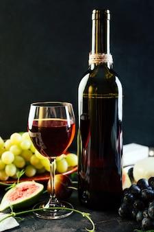 Rode wijn in een fles op een zwarte ondergrond