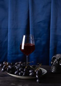 Rode wijn in een glas, druiven op een bord en een deel van een schedel op een blauwe stoffenachtergrond. het concept van magie, mystiek en esoterie.