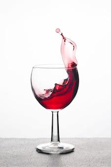 Rode wijn in een glas met spatten