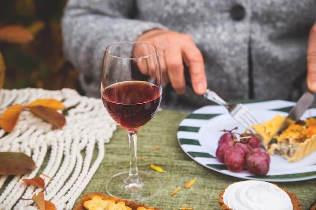 Rode wijn in een glas op een tafel van de huisvakantie in de tuin.