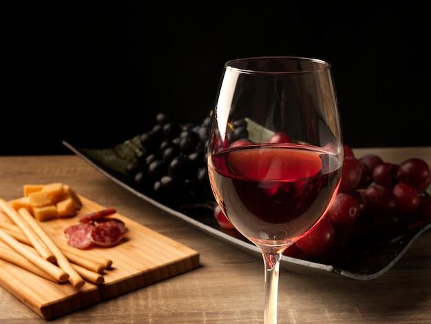 Rode wijn in een wijnglas, en op de achtergrond gesneden salami, kaas, italiaanse grissini