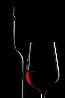 Rode wijn in glas en fles geïsoleerd op zwart