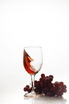 Rode wijn in glas met rode druif op witte ondergrond.