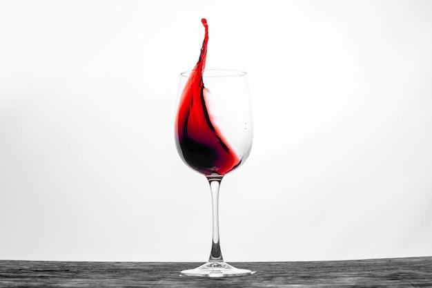 Rode wijn in het glas spatten in beweging
