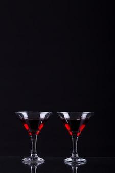 Rode wijn in twee glazen martini op een zwarte achtergrond