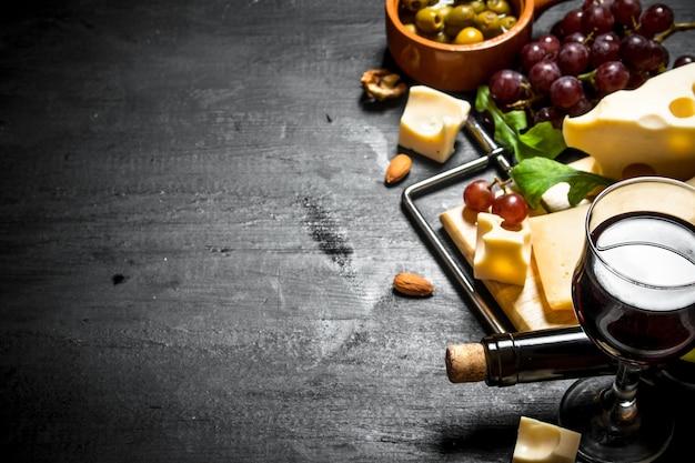 Rode wijn met een geurige kaas, olijven en amandelen.