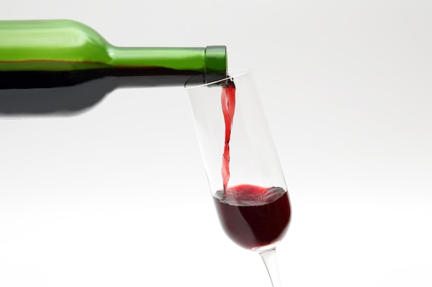 Rode wijn uit de groene fles wordt in een glas gegoten