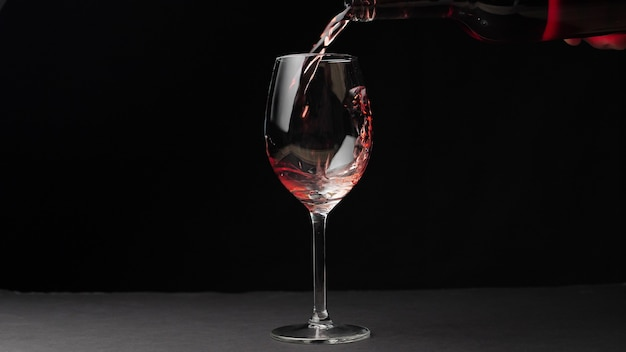 Rode wijn uit een fles gieten in een wijnglas geïsoleerd op zwarte achtergrond.