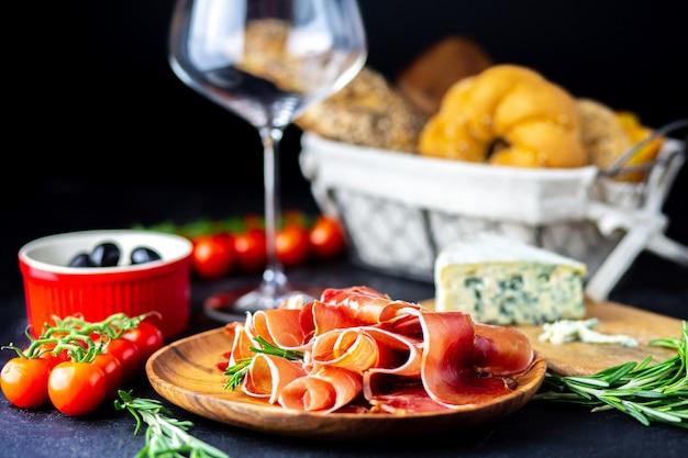 Rode wijn wordt gegoten in een bel kaas, jamon, prosciutto en olijven op een zwarte achtergrond. wijnsnack op een houten bord. brood met kaas en wijnsnacks. heerlijke snacks voor het feest.