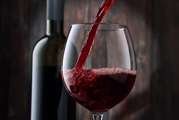 Rode wijn wordt in een glas uit een fles op een onscherpe houten achtergrond gegoten, een stroom rode wijn uit de fles wervelt in het glas