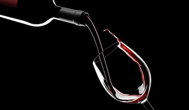 Rode wijn wordt uit de fles in een glas op zwart gegoten