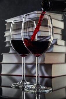 Rode wijn wordt uit een fles in een glas gegoten tegen de achtergrond van een stapel boeken