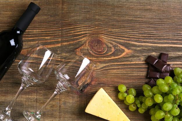 Rode wijnfles, druif, kaas en glazen over houten tafel. bovenaanzicht met kopie ruimte. stilleven. plat leggen