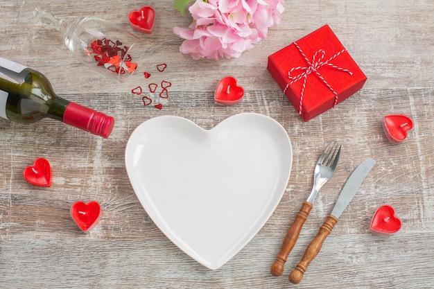Rode wijnfles en liefde geschenkdoos, kaarsen, bloemen