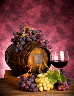 Rode wijnfles en wijnglas op wodden vat