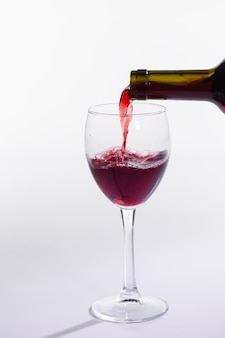 Rode wijnfles giet glas op witte achtergrond