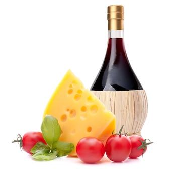 Rode wijnfles, kaas en basilicumverlofstilleven dat op wit knipsel wordt geïsoleerd als achtergrond. italiaans eten concept.