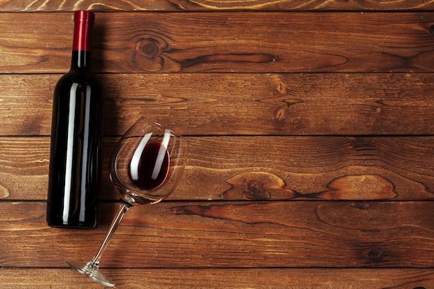 Rode wijnfles, wijnglas en kurketrekker op houten lijstachtergrond