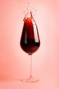 Rode wijnplons in een glas, dynamisch beeld, selectieve nadruk.