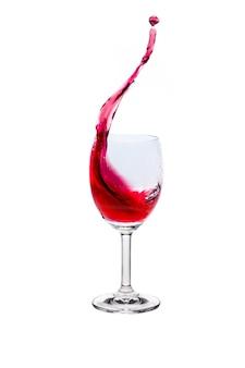 Rode wijnplons in glas op witte achtergrond.