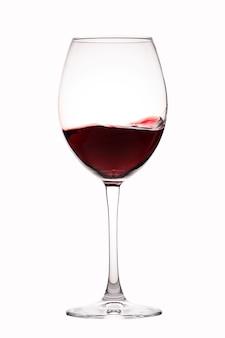 Rode wijnplonsen in een glas op wit