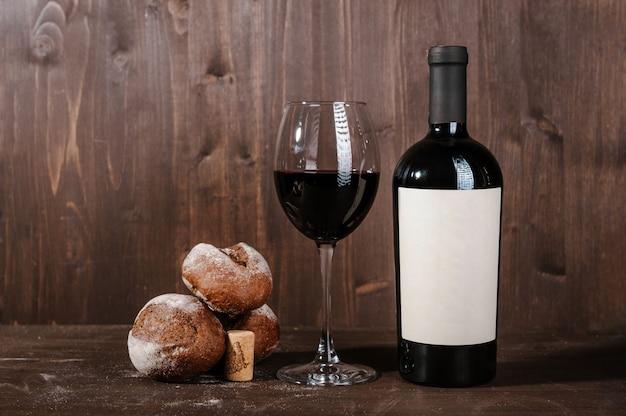 Rode wijnsamenstelling met brood, twee flessen in vakje en wijnglas op houten lijst