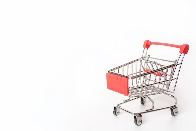 Rode winkelwagentje of supermarkt winkelwagen op witte achtergrond met kopie ruimte