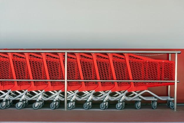 Rode winkelwagentjes op een rij bij een muur