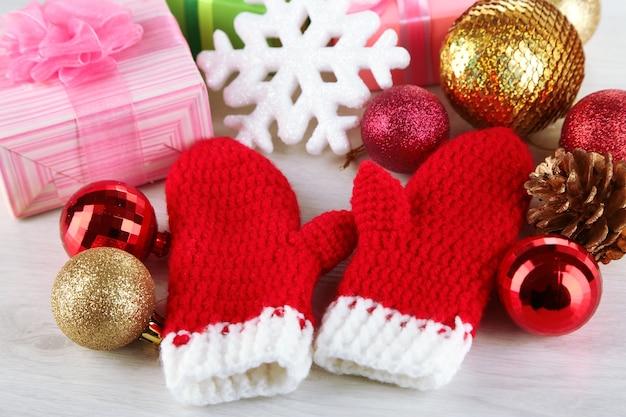 Rode winterwanten met kerstspeelgoed op houten tafel