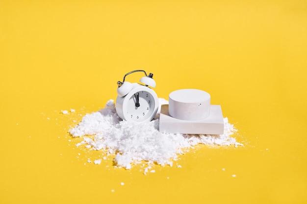 Rode witte wekker met sneeuw op gele achtergrond en podium voor product. creatieve kerstverkoop. hoge kwaliteit foto