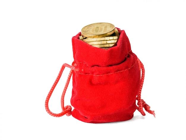 Rode zak die met muntstukken wordt gevuld die op wit worden geïsoleerd. het concept van het sparen van contant geld.