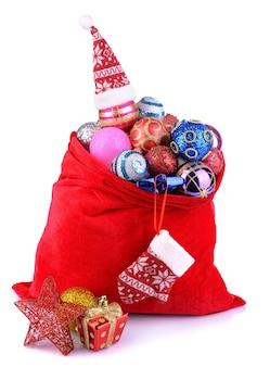 Rode zak met kerstmisspeelgoed dat op wit wordt geïsoleerd