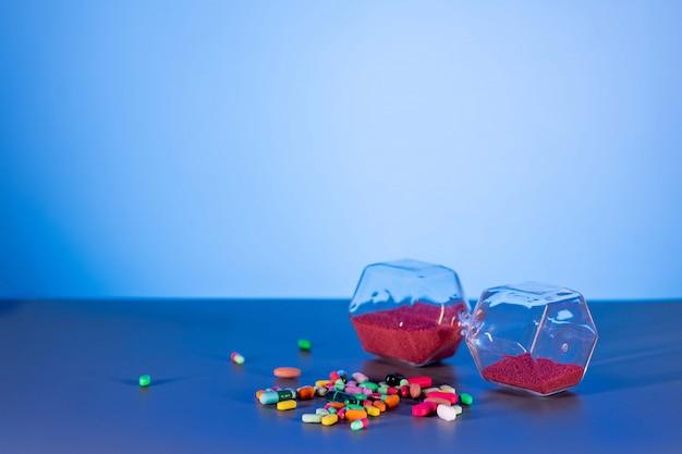 Rode zandloper die naast een handvol pillen en pillen ligt. het concept van farmacologie.