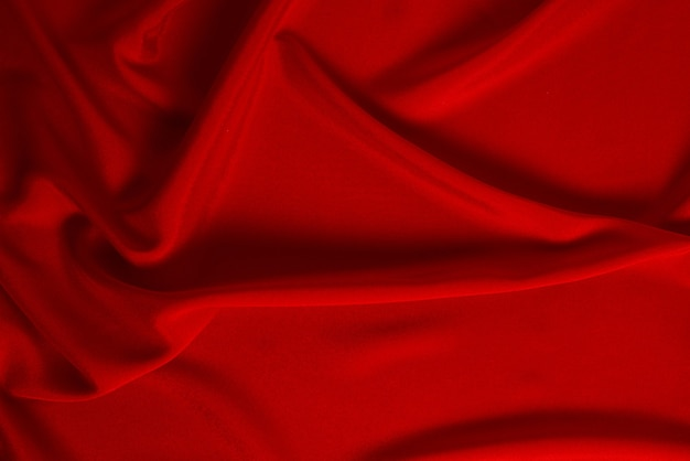 Rode zijde of satijnen luxe stoftextuur kan als abstract oppervlak worden gebruikt