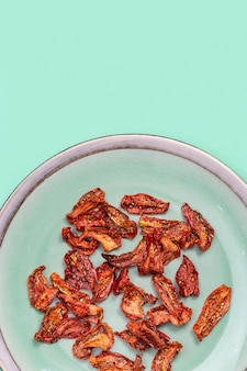 Rode zongedroogde tomaten in keramische plaat smakelijke plakjes tomaat met kruiden en olijfolie.
