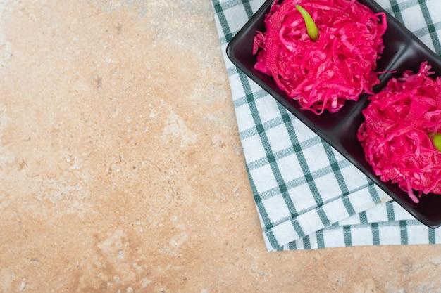 Rode zuurkool salades op zwarte plaat met tafellaken